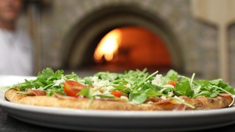 The Italiana pizza is topped with mozzarella and Romano cheeses, plum tomatoes, fresh basil and garl