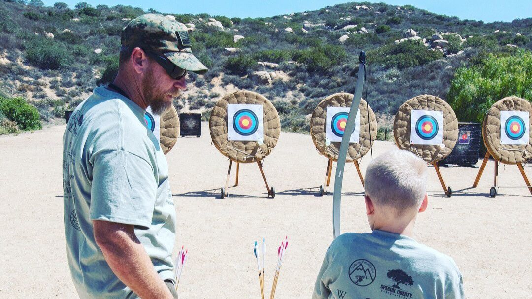 Veteran Mike Brown guides Alex Turpen, one of The Special Liberty Project's Gold Star children, at the archery range at Lake Poway.
