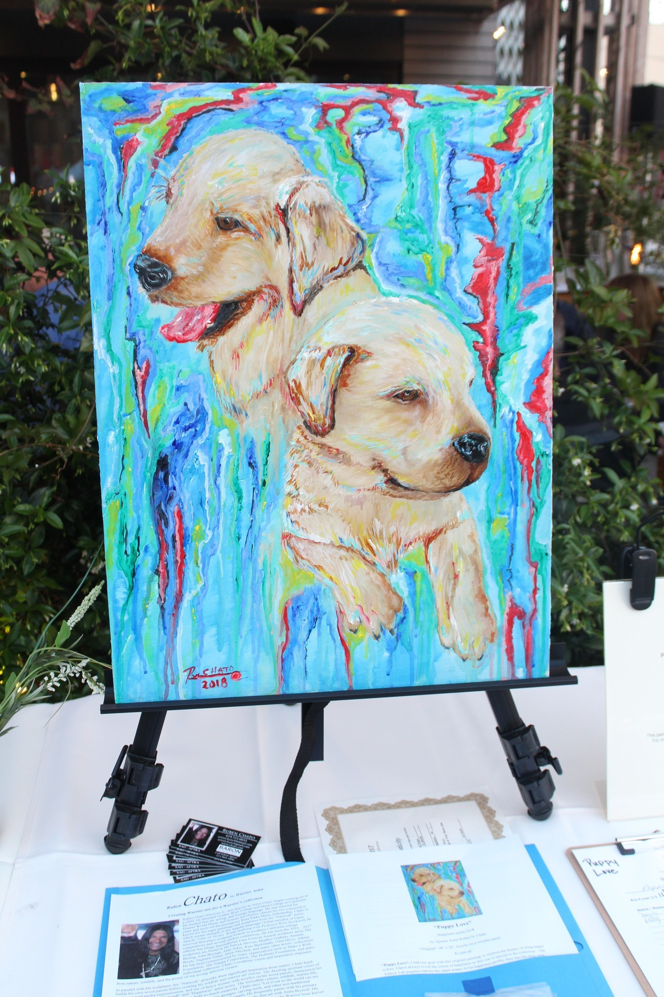 Among the items up for silent auction are 'Puppy Love,' an acrylic-on-wood by Apache artist Ruben H. Chato, valued at $1,600.