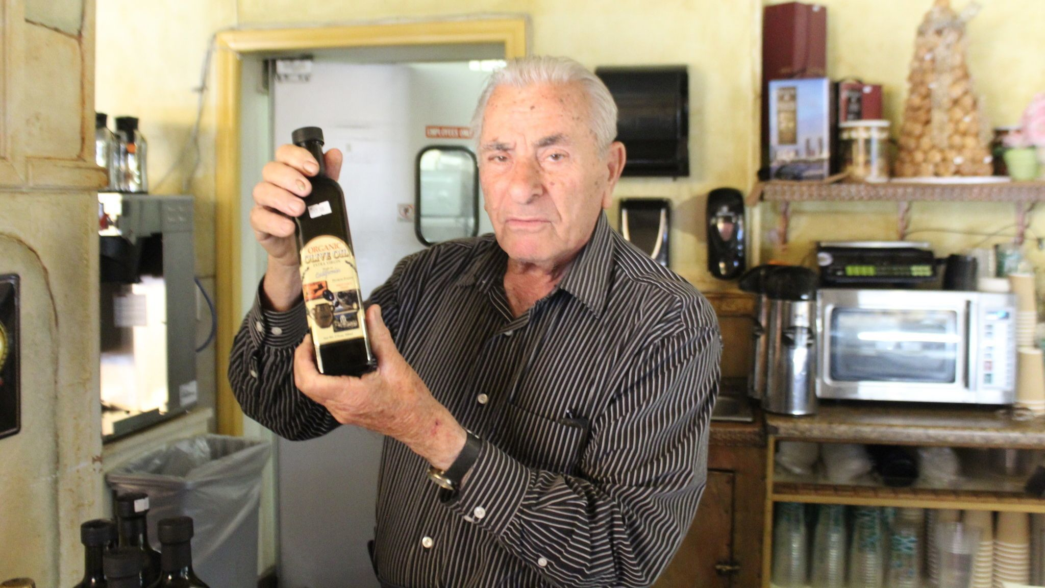 George Petrou shows off the olive oil he manufactures and sells in his second career.