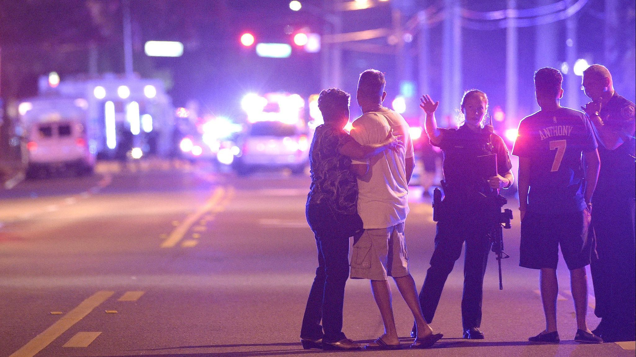 Orlando Police officers direct family members away from a multiple shooting at a nightclub in Orland