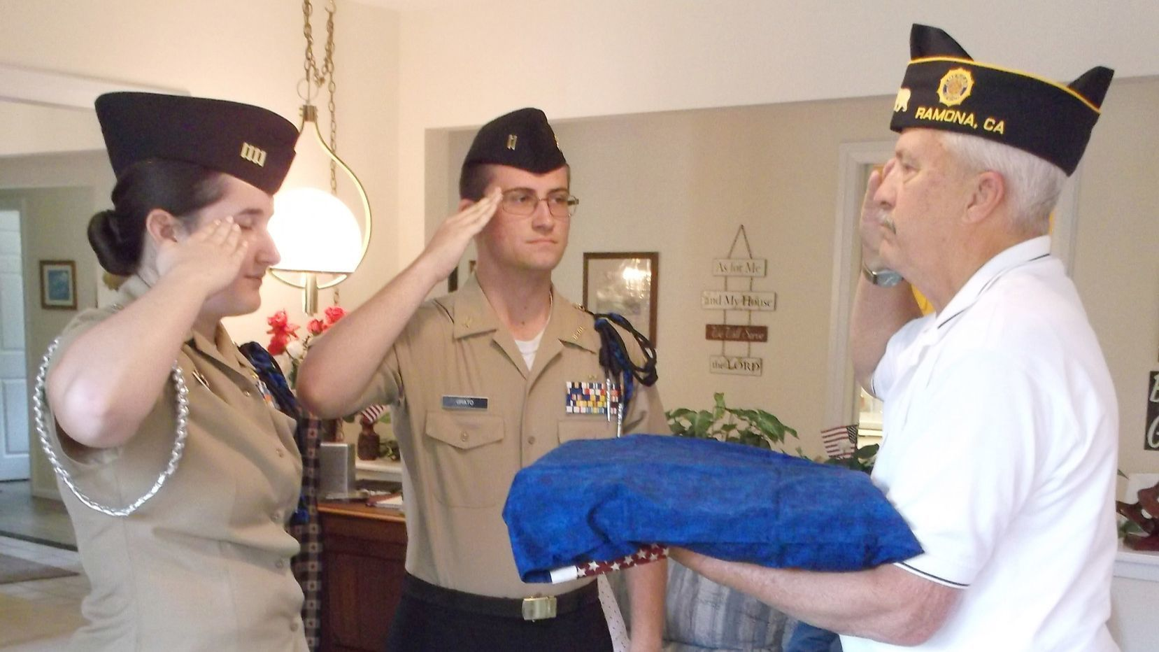 Holding his Quilt of Valor, Michael Thweatt returns a salute from NJROTC cadets Marissa Houry and Michael Grato.