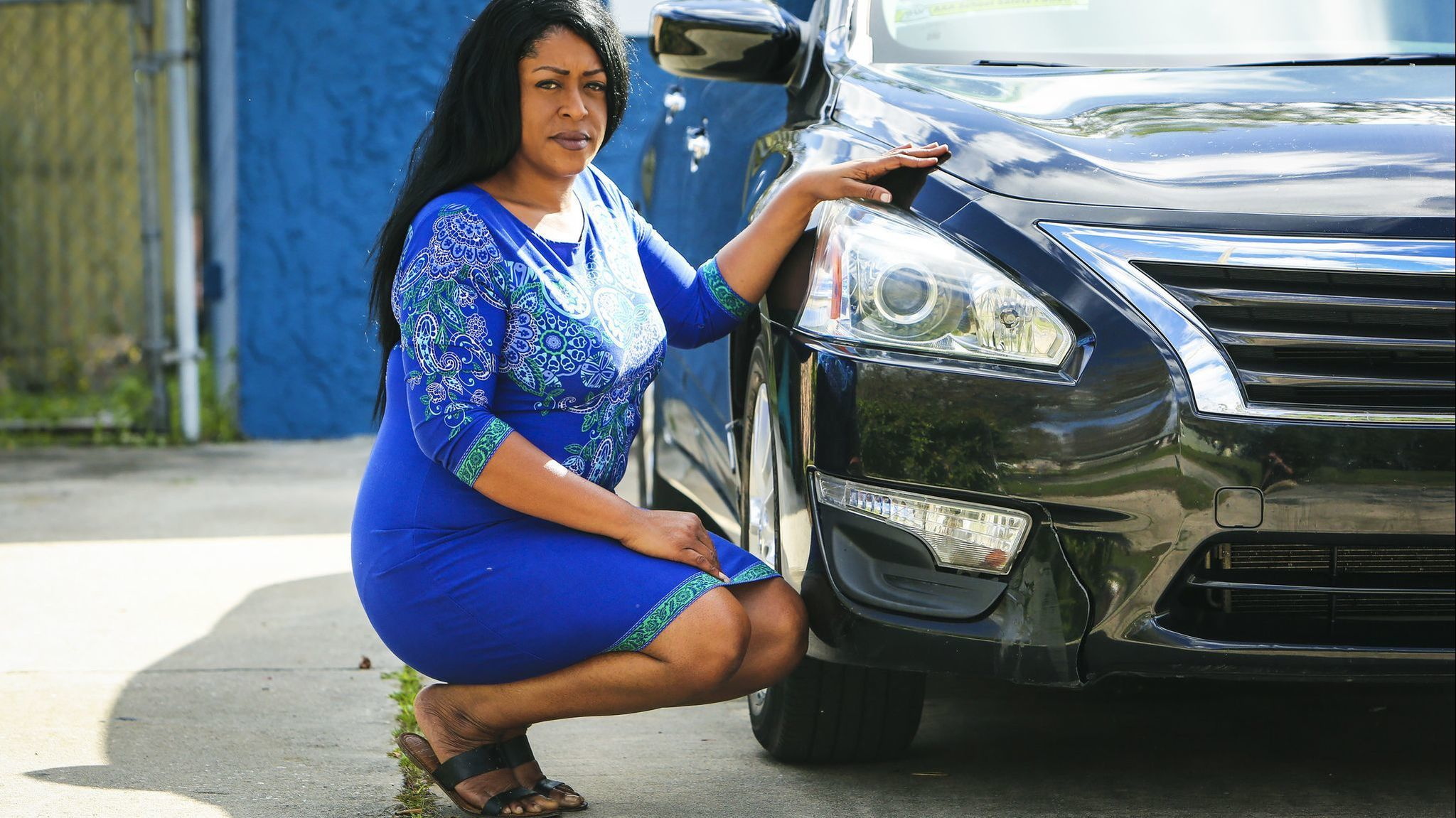 Adrienne Brown-Hayes shows next to her car that suffered damage to the right front bumper after she