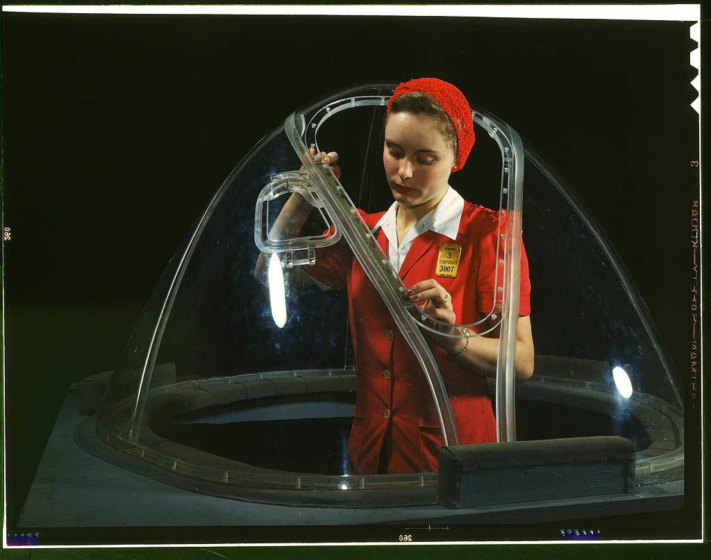 This girl in a glass house is putting finishing touches on the bombardier nose section of a B-17F na