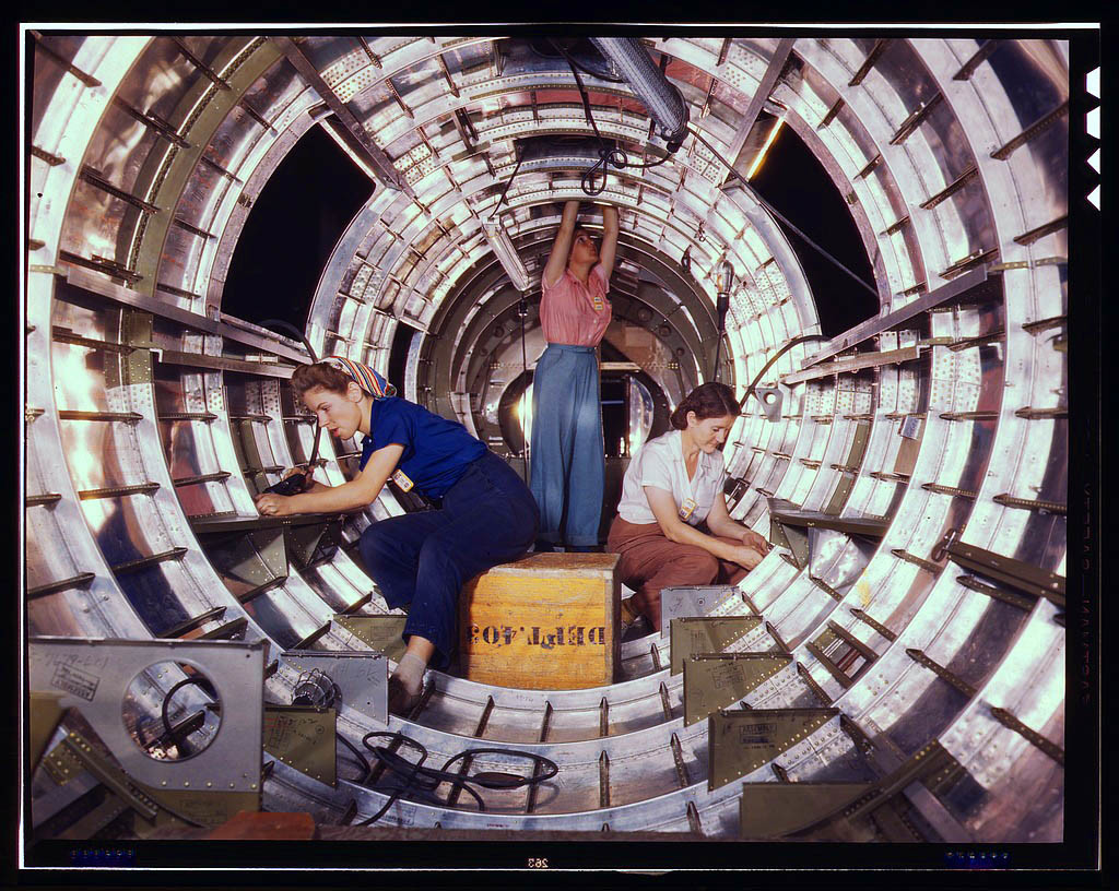 Women workers install fixtures and assemblies to a tail fuselage section of a B-17 bomber at the Dou