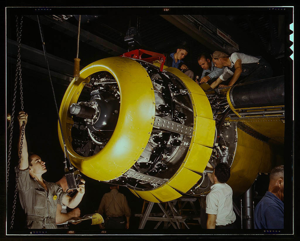 Mounting motor on a B-25 bomber, at North American Aviation, Inc., plant in Inglewood, Calif. 1942