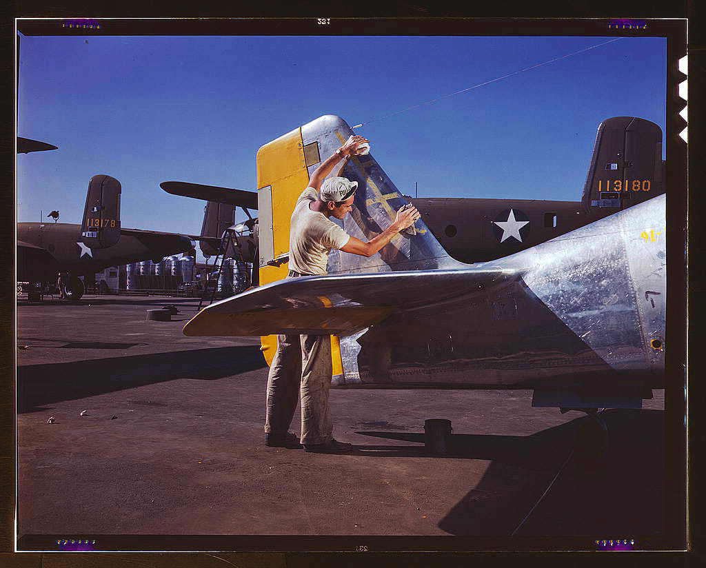 On North American's outdoor assembly line, a painter cleans the tail section of a P-51 fighter prior