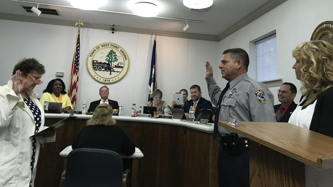 Tim Sawyer being sworn in as West Point Police Department's new police chief at West Point town council's Tuesday night meeting by King William County Circuit clerk Patricia Norman, with his wife Betty standing beside him. (Ashley Luck)