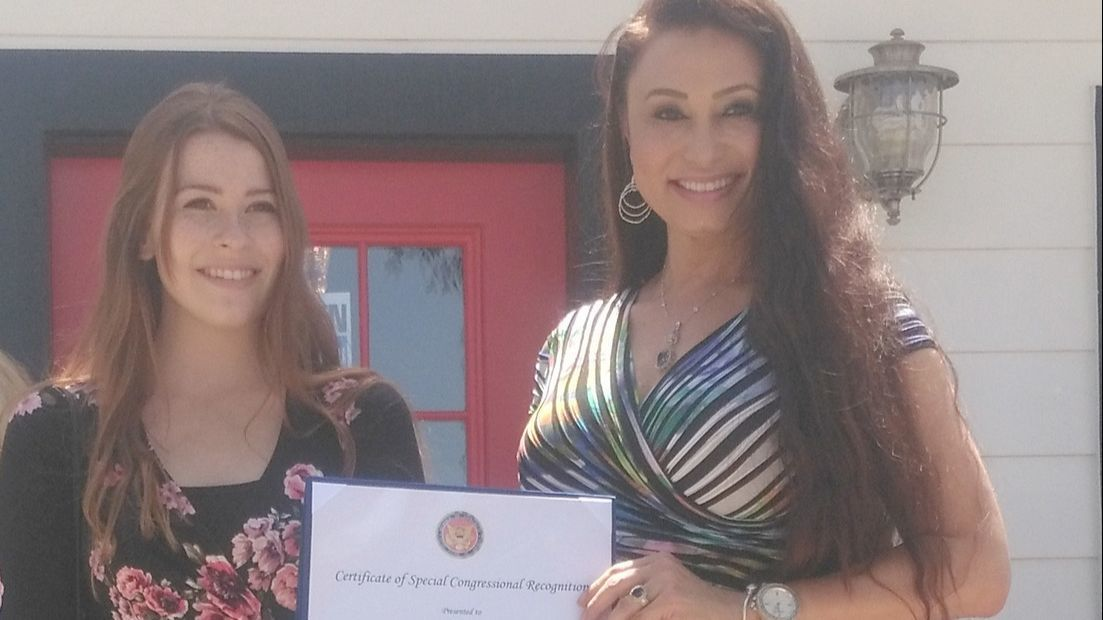 Shannon Linder, administrative support for Congressman Duncan Hunter's office, gives a certificate of special congressional recognition to LelLani Vidal, owner of The Lipo Lounge.