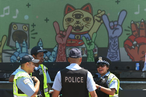Police officers are posted in front of an information display at Lollapaloozaon Aug. 3, 2018, in Chicago.