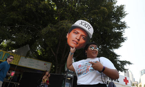 A festivalgoer holds a cutout of musician Bruno Mars at Lollapaloozaon Aug. 3, 2018, in Chicago.