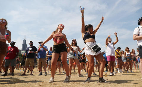 Festivalgoers dance to the music of Bomba Estereo at Lollapalooza Saturday, Aug. 4, 2018, in Chicago.