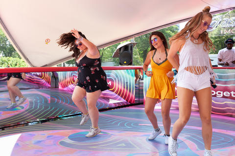Eli Carrano, Ashley Ptak and Adriana Gutowski dance on a stage that Asics created to provide boomerangs for Lollapalooza attendees. Saturday, August 4, 2018.