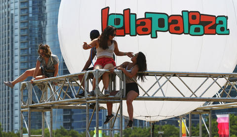 Festivalgoers climb on scaffolding while watching Sir Sly at Lollapalooza Saturday, Aug. 4, 2018, in Chicago.