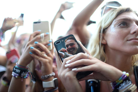 Chaney Lehr holds her phone, whose case features an image of Post Malone, at Lollapaloozaon Aug. 3, 2018, in Chicago.