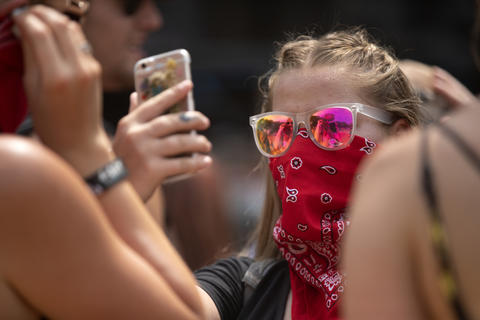 A festivalgoer uses a handkerchief to keep dust out of her face at Lollapalooza Sunday, Aug. 5, 2018, at Grant Park in Chicago.