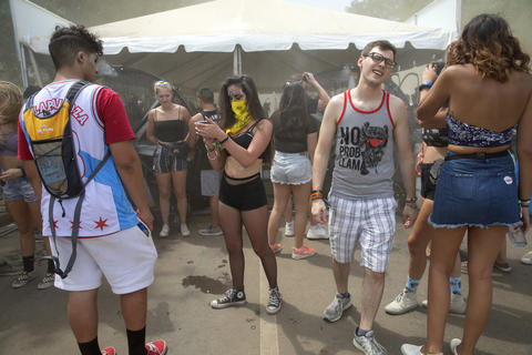 Festivalgoers stand in front of large fans on a hot day four of Lollapalooza Sunday, August 5, 2018, at Grant Park in Chicago.