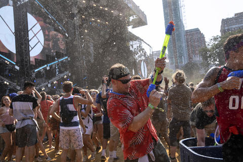 People spray festival goers with water during Herobust's set on a hot day four of Lollapalooza Sunday, Aug. 5, 2018, at Grant Park in Chicago.