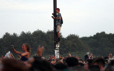 A man climbs a pole to watch Lil Uzi Vert on Sunday, Aug. 5, 2018 at Lollapalooza in Grant Park.