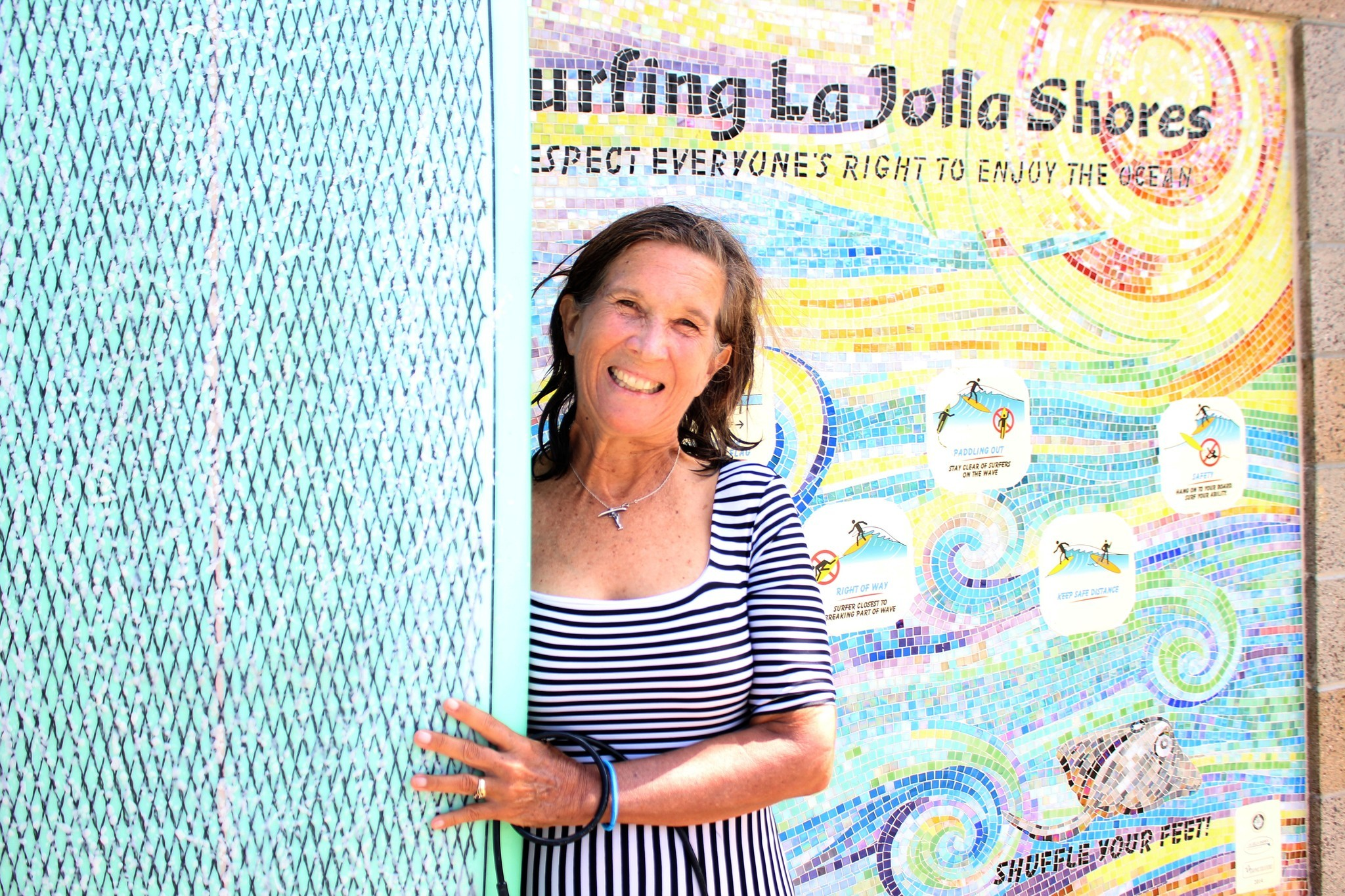 Lorraine Schmalenberger, president of the La Jolla Shores Surfing Association, poses with her board in front of a $10,000 mural that WindanSea Surf Club donated the fi