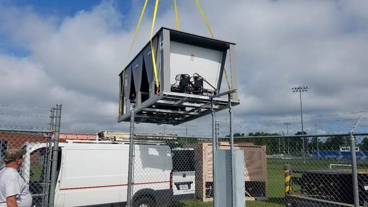 Crane lifting HVAC equipment