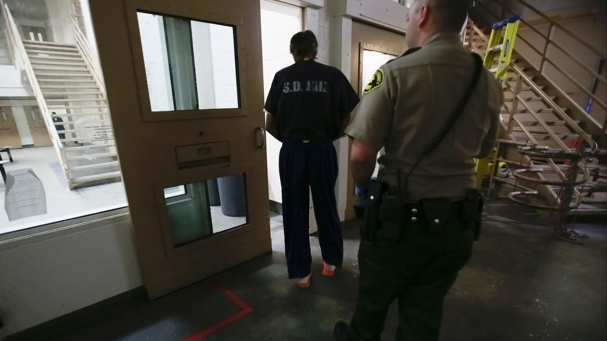 A Sheriff's Deputy escorts an inmate into one of the jail sections in the main line at downtown Central Jail.