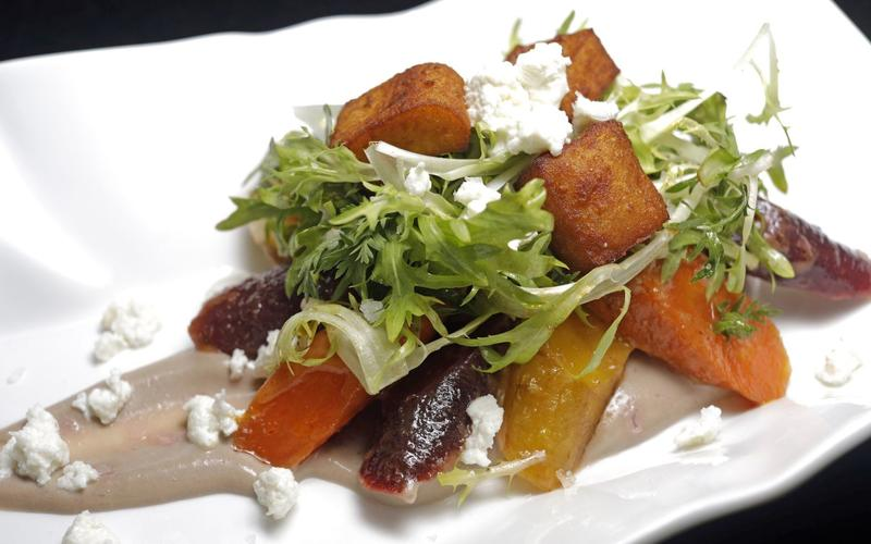 Station's carrot salad with pomegranate curd, fresh cheese, chickpea fritters, bitter greens and harissa vinaigrette
