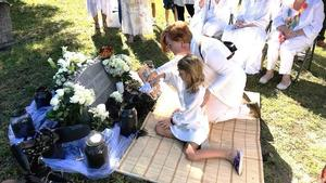 Dawn Neff and her 8-year-old granddaughter scoop soil from the grave of July Perry into a glass jar at a ceremony Saturday at Greenwood Cemetery.