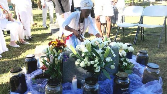Josie Onifade Lemon Allen arranges candles at the grave of July Perry