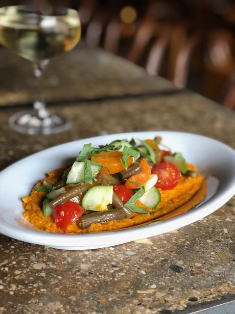 Carrot-harissa hummus with pickled beans, tomato and cucumber, served with na'a, part of the new seasonal menu items at Ada St.