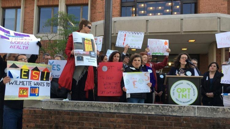 Supporters and an opponent of Cook County's wage and sick time ordinances rally in May, 2018, before one of several meetings the village board held on the issues.