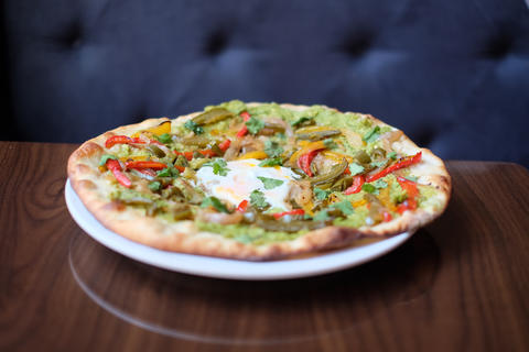 Parlay at Joy District offers a brunch buffet featuring items like this avocado pizza featuring fajita vegetables, jalapeño and a sunny-side up egg.