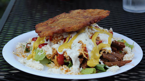 The patacon mixto fried plantain sandwich is stuffed with shredded beef, chicken, ham, cheese, lettuce, mayonnaise, mustard and ketchup.