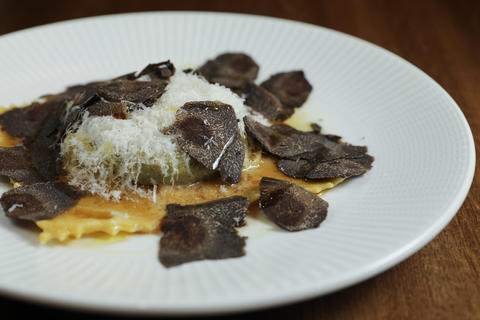 A large duck raviolo is coddled in brown butter and topped with shaved coins of black truffle.