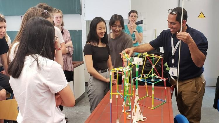 Teacher helping students build a structure