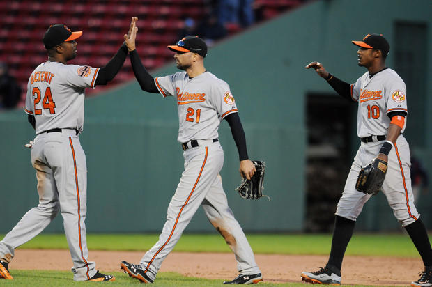 The Orioles' Wilson Betemit, left, Nick Markakis, center, and Adam Jones exchange high-fives after beating the Red Sox, 9-6, in 17 innings.