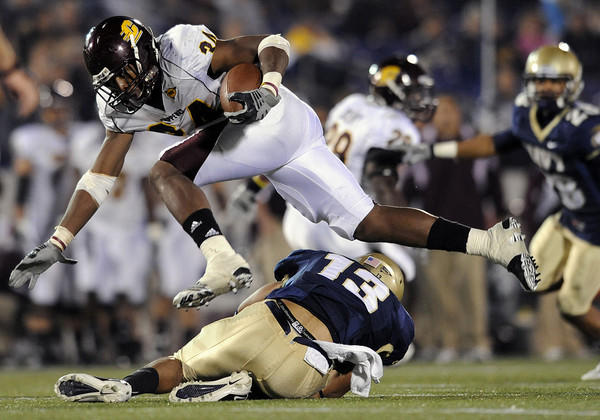 Central Michigan's Zurlon Tipton, top, jumps over and Navy's Jordan Fraser in the second half.