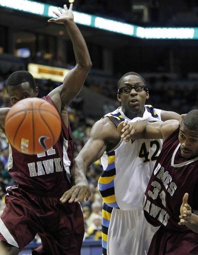 UMES' Tim Burns (left) and Neal Pitt battle for a rebound with Marquette's Chris Otule in the first half.
