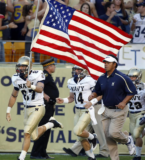 Navy coach Ken Niumatalolo runs onto the field with the Midshipmen before their game against Pitt.