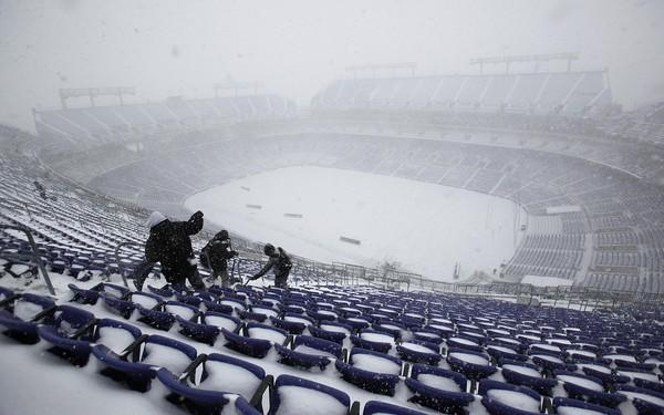 Workers remove snow from the stands at M&T Bank Stadium.
