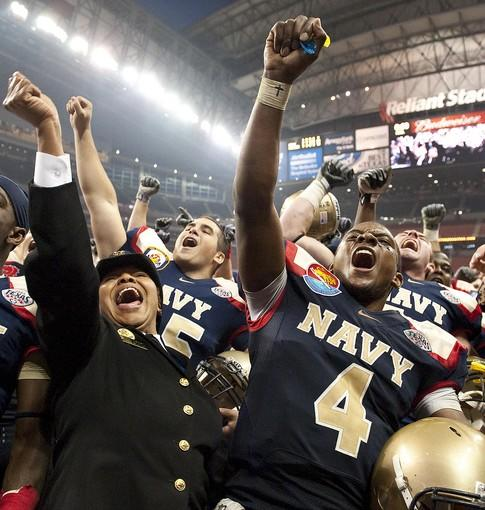 Navy quarterback Ricky Dobbs celebrates with Vonn Banks, left, after the Mids' win in the Texas Bowl.