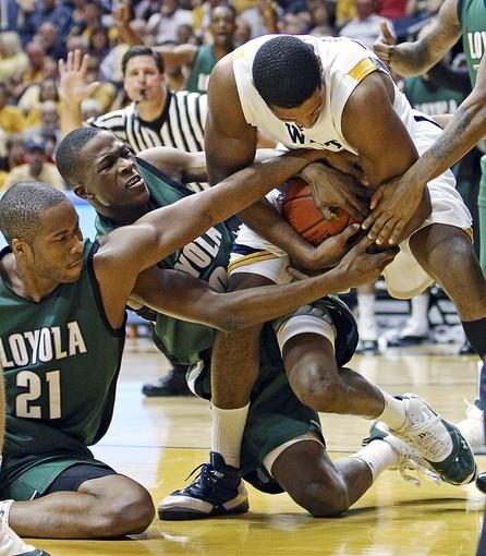 West Virginia's Wellington Smith (right) battles Loyola's Jawaan Wright (21) and J'hared Hall for possession in the first half.