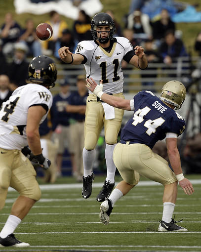 Wake Forest quarterback Riley Skinner throws a pass to fullback Mike Rinfrette while being pressured by Navy linebacker Clint Sovie in the first half.