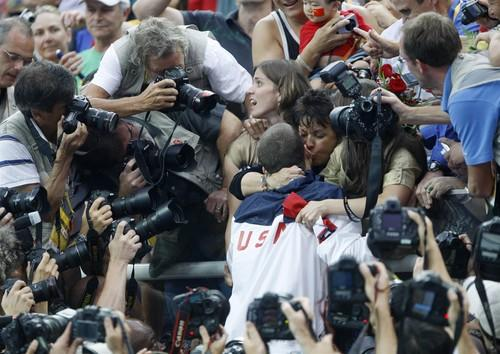 Surrounded by photographers, Michael Phelps gets a kiss from his mother, Debbie, after winning his eighth gold of the Beijing Games.