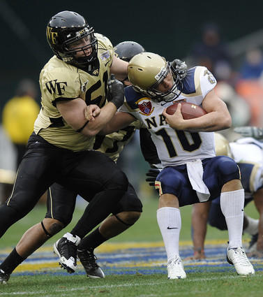 Navy quarterback Kaipo-Noa Kaheaku-Enhada (right) is tackled by Wake Forest's John Russell in the  first quarter of the EagleBank Bowl at RFK Stadium.