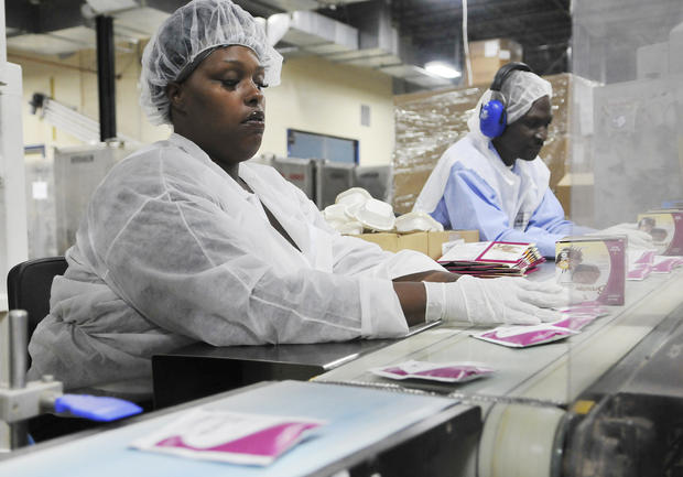 Workers at Medifast assemble brownie mix packages and pack them into boxes at the factory in Owings Mills.