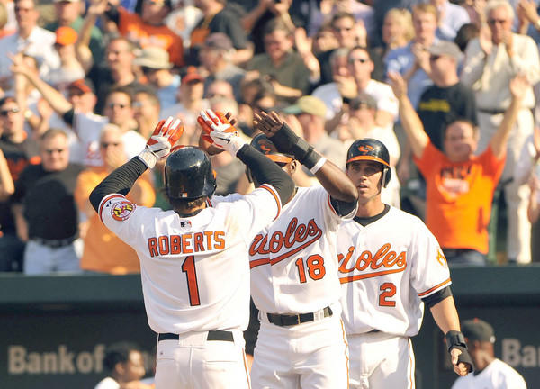 Orioles leadoff man Brian Roberts is met by teammates Felix Pie, center, and J.J. Hardy after hitting a three-run homer in the fifth inning of a 5-1 win over the Tigers at Camden Yards.