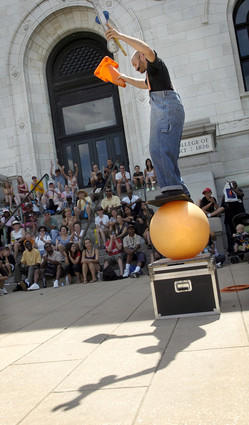 At his first appearance at Artscape, street performer Brent McCoy of Greensboro, Vermont balances himself on a board that is on top of a large rubber ball in front of the main MICA building. During his performance, McCoy juggled knives, balanced a large dolly on his chin, and involved the audience in an act.