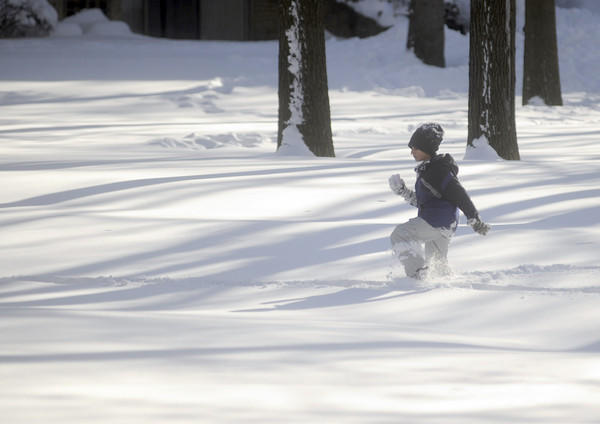 A child runs through the snow at the Americana apartment complex in Glen Burnie.