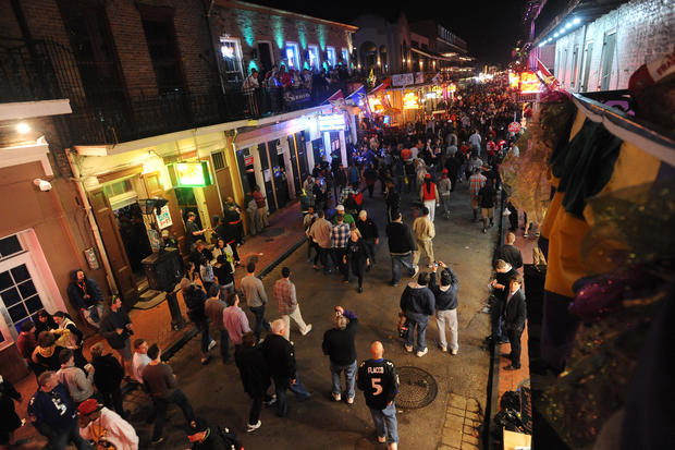 Crowds of people walk down Bourbon Street in New Orleans on Friday night.